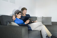 Happy casual couple relaxing on couch using tablet - SBOF01798