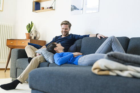 Happy casual couple relaxing on lounge couch in their modern living room - SBOF01801