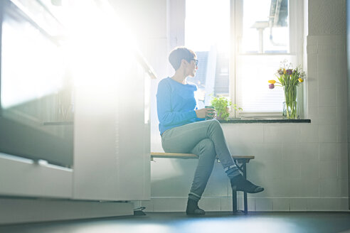 Short-haired woman sitting on bench in kitchen at the window holding coffee mug - SBOF01804