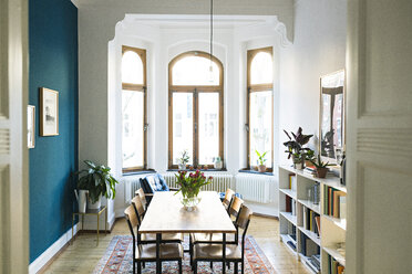Wooden table and chairs in modern living room with large window front in stylish apartment - SBOF01807