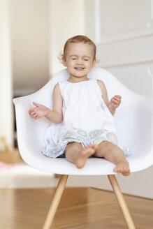 Deutschland, München, Mädchen 2 Jahr sitzt auf einem Stuhl, Portrait - DIGF05853