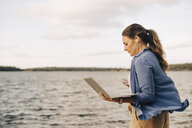 Confident mature woman using laptop while talking on mobile phone by lake - MASF11079