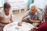 Senior people playing cards at table in retirement home - MASF11130