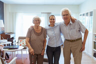 Portrait of smiling young woman with grandparents standing together in nursing home - MASF11136
