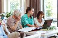 Healthcare worker and elderly women with laptop and medical reports at nursing home - MASF11139