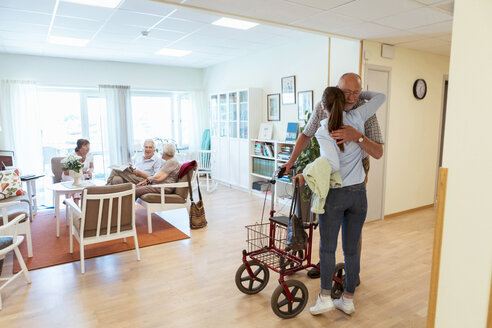 Young woman embracing grandfather during visit at nursing home - MASF11142