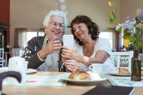 Senior couple taking selfie using mobile phone during breakfast at nursing home - MASF11145