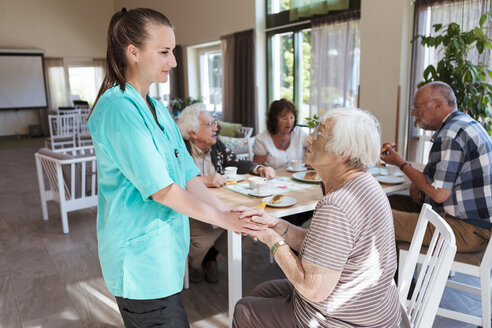 Nurse comforting senior woman while having breakfast at nursing home - MASF11151