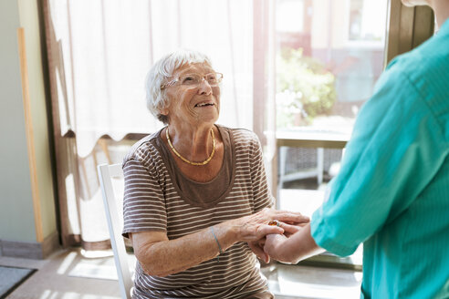 Smiling senior woman holding hands of healthcare worker at nursing home - MASF11154