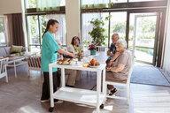 Female caretaker serving breakfast to senior people in nursing home - MASF11163