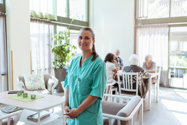 Portrait of smiling female healthcare worker with senior people in background at nursing home - MASF11169