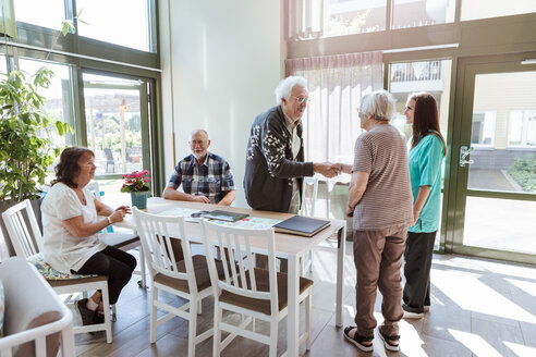 Senior man and woman shaking hands near friends and nurse at nursing home - MASF11175