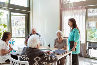 Female healthcare worker talking with elderly people at nursing home - MASF11178