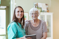 Portrait of smiling senior woman and nurse with digital tablet at home - MASF11181