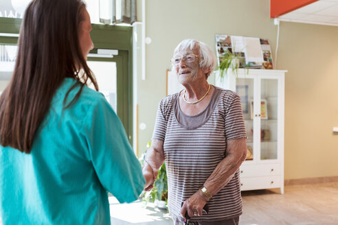 Smiling elderly woman shaking hands with nurse at nursing home - MASF11184