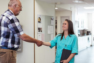 Smiling young nurse shaking hand with senior man at nursing home - MASF11190