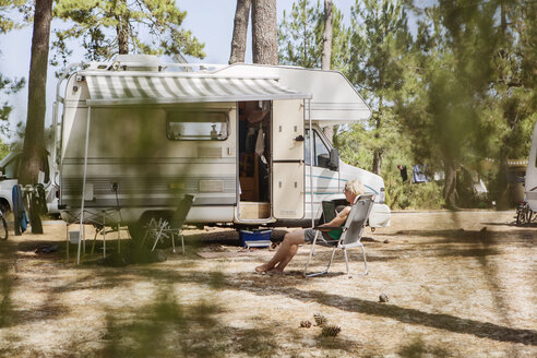 France, Gironde, woman sitting in front of camper on a camping ground using digital tablet - JATF01132