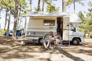 France, Gironde, happy couple sitting in front of camper on camping ground - JATF01135