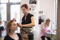 Female hairdresser drying customer's long hair in salon - MASF11196