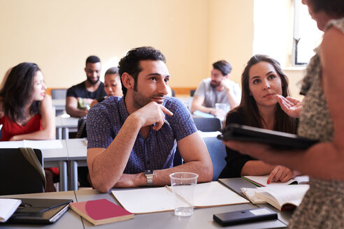 Male and female students looking at teacher explaining in classroom - MASF11274