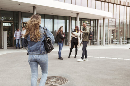 Rear view of woman walking towards friends at university campus - MASF11319