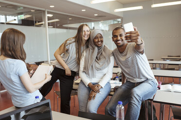 Smiling man taking selfie with female friends on smart phone at classroom - MASF11328