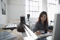 Female photographer online shopping at computer, ordering with credit card in art studio - HEROF22654