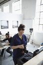 Female photographer working with digital camera and lens in art studio - HEROF22693
