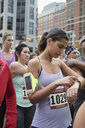 Female marathon runner checking smart watch, waiting at starting line on urban street - HEROF22696
