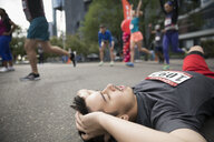Exhausted male marathon runner collapsing at finish line - HEROF22699