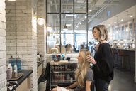Female hair stylist and customer talking, planning in hair salon - HEROF22759