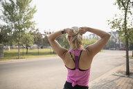 Female runner fastening ponytail on sunny sidewalk - HEROF22768