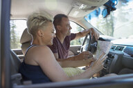 Couple looking at map in car on road trip - HEROF22780