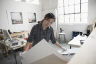 Focused female photographer reviewing large photography print in art studio - HEROF22816