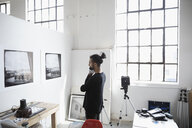Focused male photographer examining large photography print hanging on wall in art studio - HEROF22846