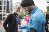 Husband helping smiling wife put on marathon bib on urban street - HEROF22849