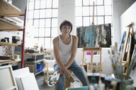 Portrait confident, serious female painter with palette painting at canvas on easel in art studio - HEROF22945