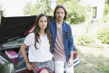 Portrait serious young couple unpacking car - HEROF22966