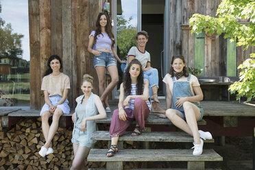 Portrait female friends sitting on wood cabin steps - HEROF22969