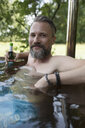 Portrait hipster man with beer relaxing and drinking beer, soaking in hot tub - HEROF22981