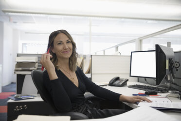 Portrait confident businesswoman working at desk in office cubicle - HEROF23005