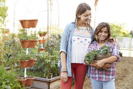 Portrait Latina sisters harvesting vegetables in garden - HEROF23026
