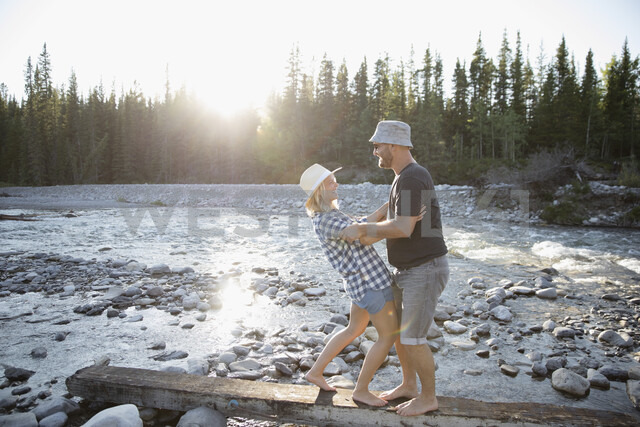 Playful barefoot couple on wood plank along sunny summer stream - HEROF23053 - Hero Images/Westend61