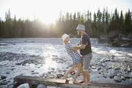 Playful barefoot couple on wood plank along sunny summer stream - HEROF23053
