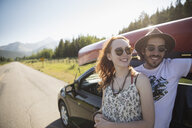 Portrait smiling, affectionate young couple outside car with canoe at sunny summer rural roadside - HEROF23065