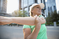 Mature female runner stretching arm on urban street - HEROF23122