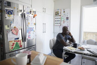 Mature African American man talking on cell phone and working at laptop at kitchen table - HEROF23179