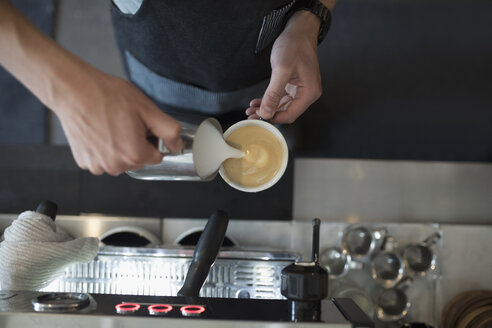 Overhead view male barista pouring milk foam into cappuccino in cafe - HEROF23197