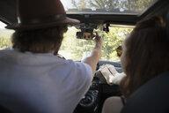 Man adjusting rear view mirror in car on road trip - HEROF23209