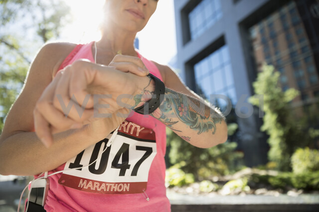 Tattooed female marathon runner checking smart watch in urban park - HEROF23242 - Hero Images/Westend61